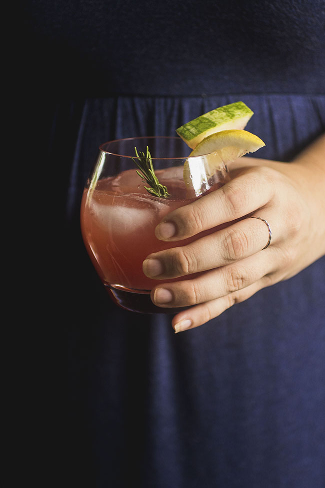 Woman in a blue dress holding a watermelon cocktail.