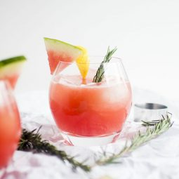 Pink cocktail garnished with a watermelon slice and a rosemary sprig.