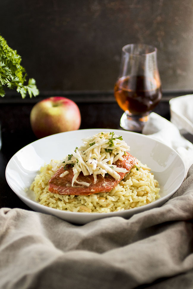 Salmon fillet with rice pilaf and light coleslaw in a white bowl on a dark brown background with a light brown linen napkin