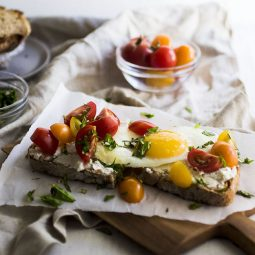 Sunny side up egg on toast with cherry tomatoes and chopped basil.