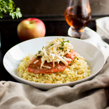 Salmon filet on top of rice pilaf with coleslaw in a white bowl on a dark brown background