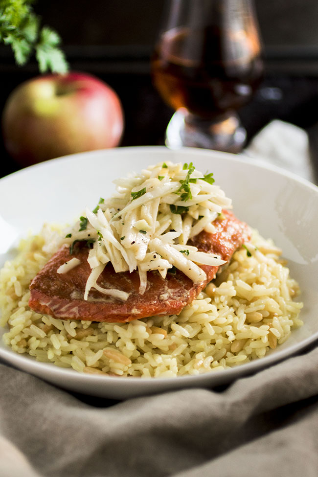 Shallow white bowl filled with rice pilaf topped with a baked piece of salmon and sliced apples sitting on a light brown napkin with a dark background