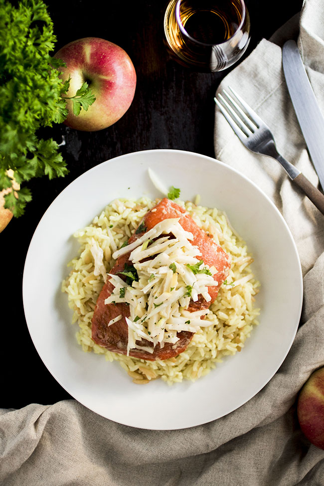 Overhead photo of rice pilaf with salmon and apple slaw in a shallow white bowl on a dark background surrounded by apples and fresh parsley