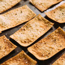 Homemade crackers on a dark baking sheet.