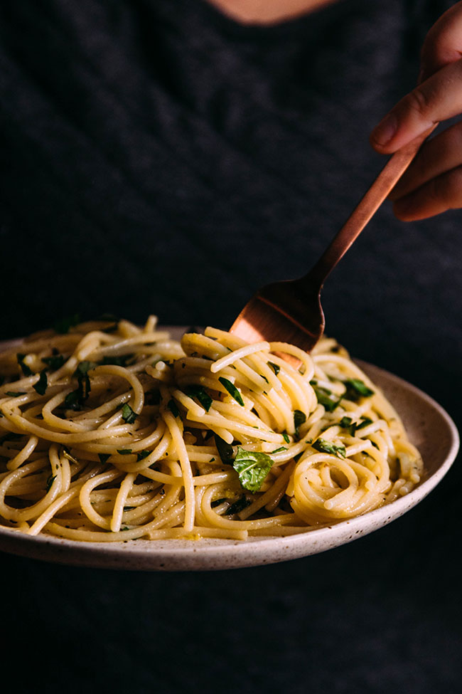 Close up photo of woman's hands holding a plate with spaghetti and fresh herbs with a copper fork