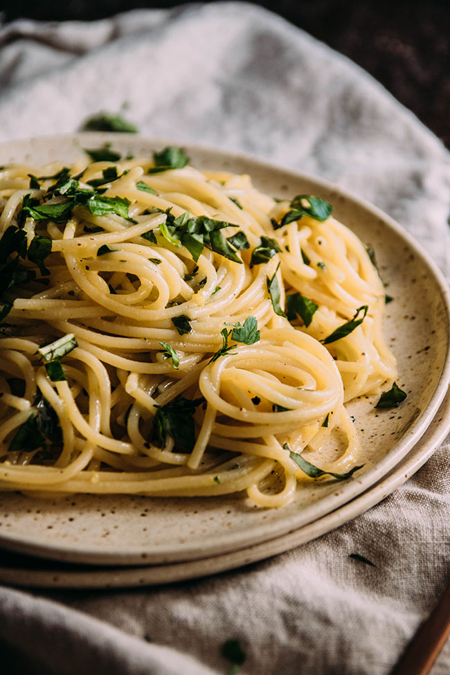 Close-up side photo of spaghetti pasta with fresh herbs on two stacked light brown plates with a cream linen napkin.