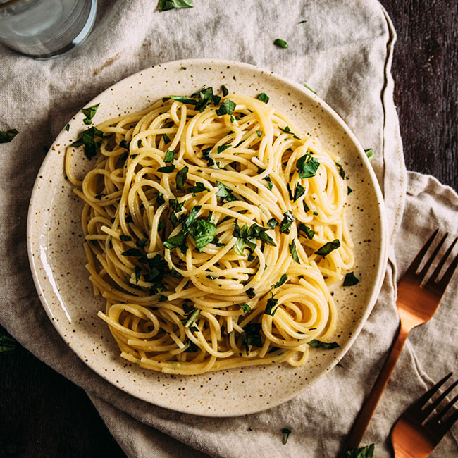 Overhead photo of spaghetti with herbs on a light brown plate with a light brown linen napkin on a dark background.