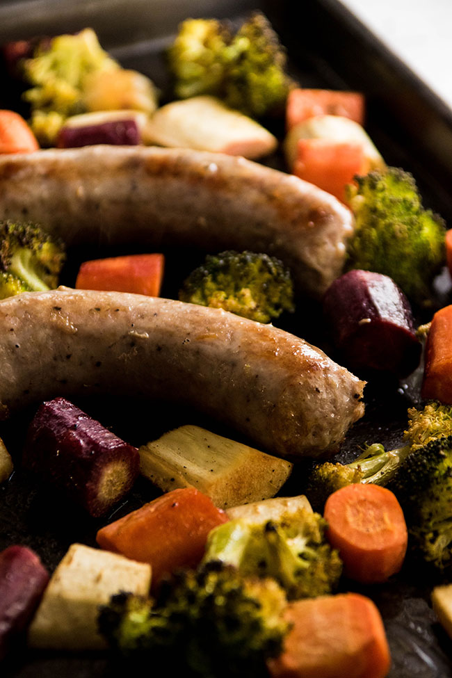 Close-up side photo of cooked polish sausage surrounded by chopped carrots, parsnips, and broccoli on a dark grey sheet pan.