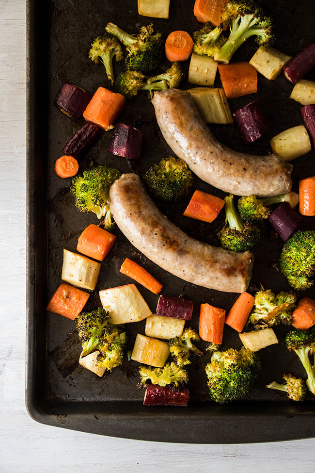 Overhead photo of cooked polish sausage and chopped vegetables on a dark sheet pan.