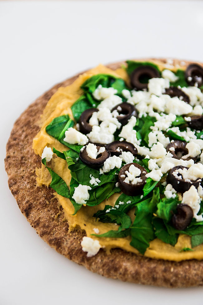 Hummus, spinach, black olives and feta cheese on a piece of wheat pita bread with a white background