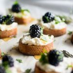 Blackberry crostini on a baking sheet lined with white parchment paper.