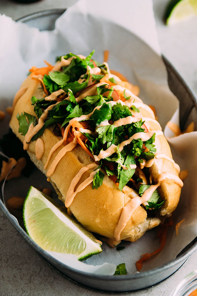 Side photograph of a banh mi sandwich in a metal dish next to a lime wedge