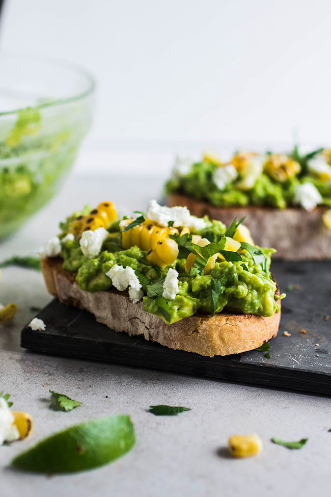Side photo of two pieces of toast topped with mashed avocado and grilled corn on a dark grey serving tray and a white background