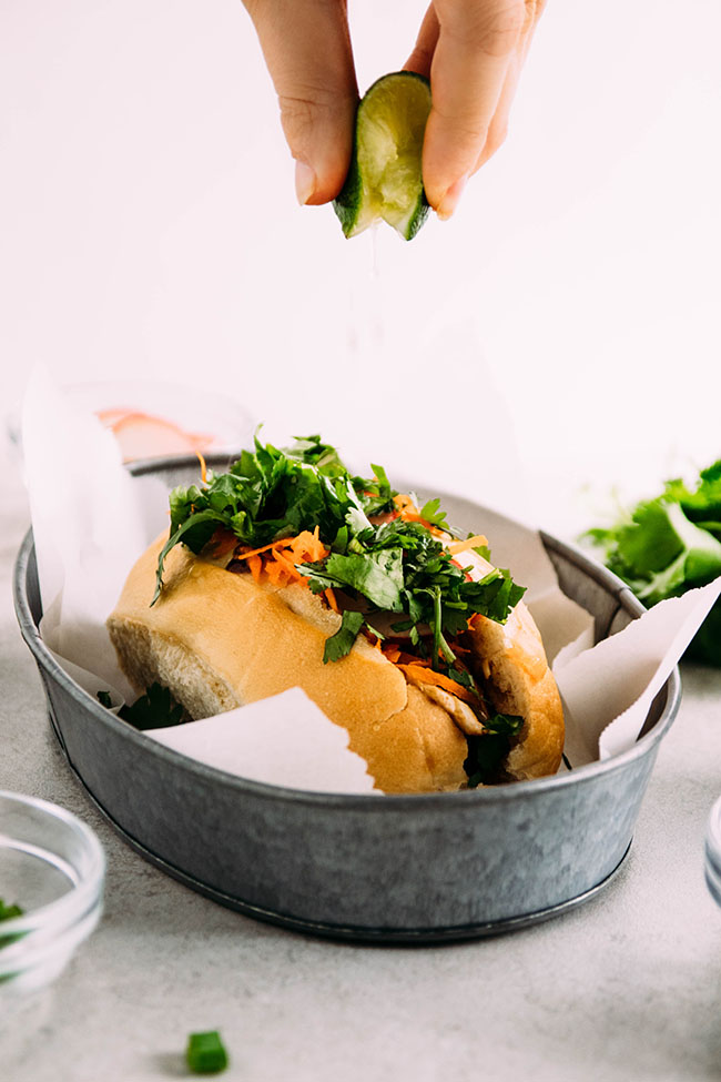 Side photograph of a banh mi sandwich in a metal container with a hand squeezing a fresh lime wedge over the top