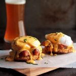 Two eggs benedict servings on a wooden cutting board in front of a glass of beer.