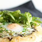 Close up of pizza topped with fresh arugula and a baked egg.