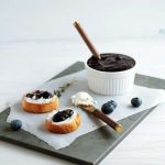 A dish of blueberry jam next to two crostini on a dark platter.