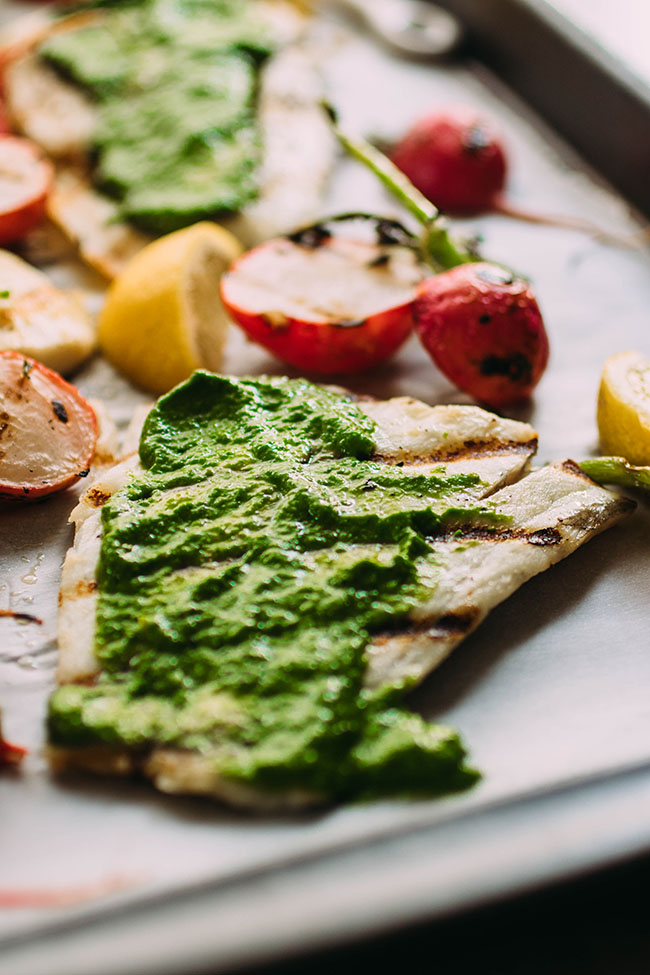 Side photo of barramundi fish fillet on a sheet pan, topped with bright green pesto with grilled radishes in the background.
