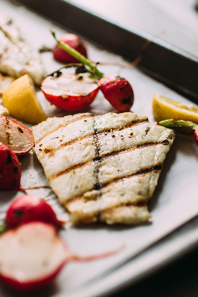 Side photo of grilled barramundi fillet on a sheet pan surrounded by grilled radishes and lemon wedges.