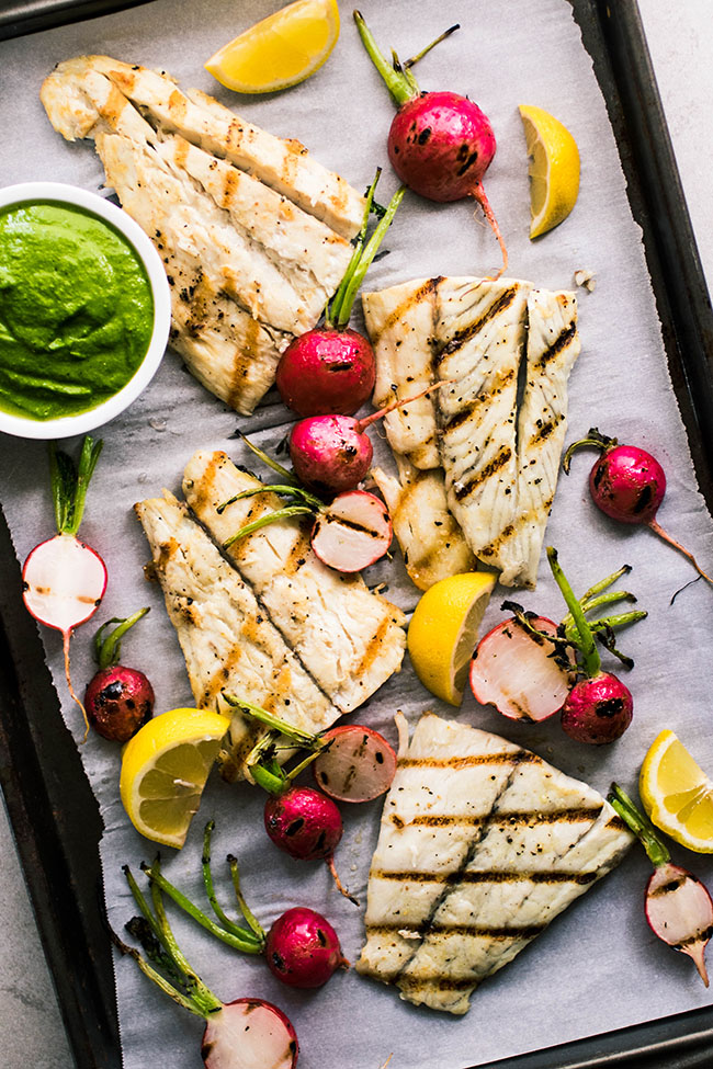 Overhead photo of grilled barramundi fish fillets on a sheet pan lined with parchment paper and surrounded by grilled radishes and lemon wedges.