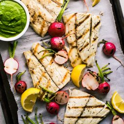 Grilled barramundi on a sheet pan with radishes, lemon wedges, and a bowl of pesto.