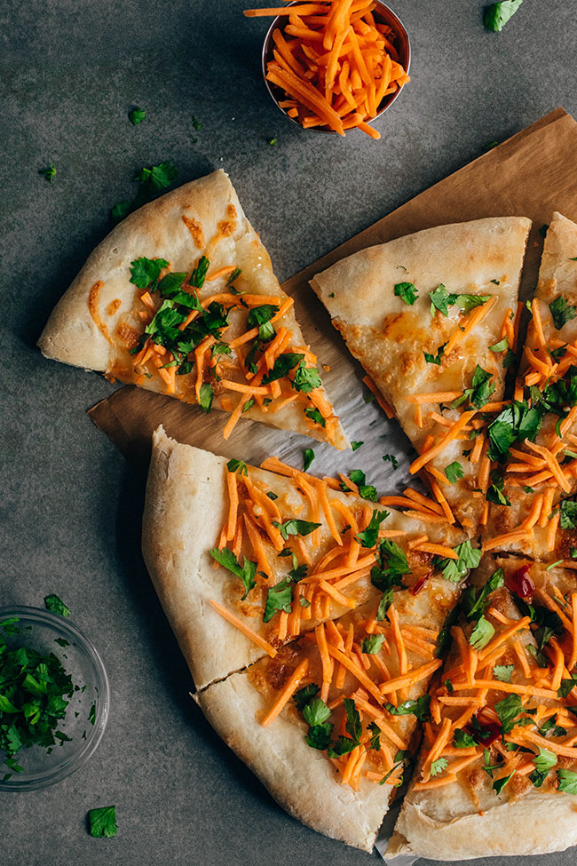 Overhead photo of pizza topped with shredded carrots and cilantro with one slice pulled out on a dark background
