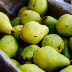 Large cardboard box filled with green pears.