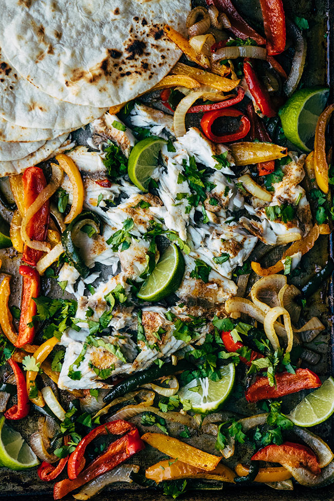 Dark sheet pan with roasted barramundi, peppers, and onions topped with fresh cilantro.