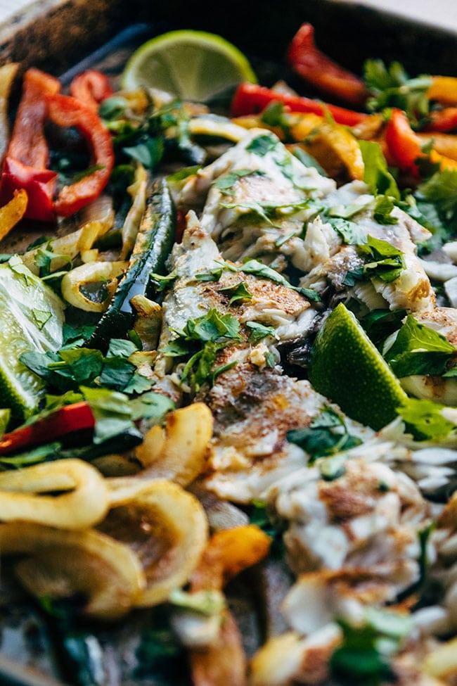 Flaked barramundi on a sheet pan with veggies.