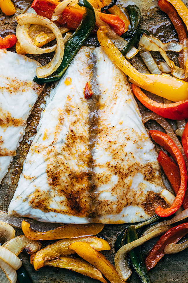 Close up of a baked barramundi fillet topped with spice rub.