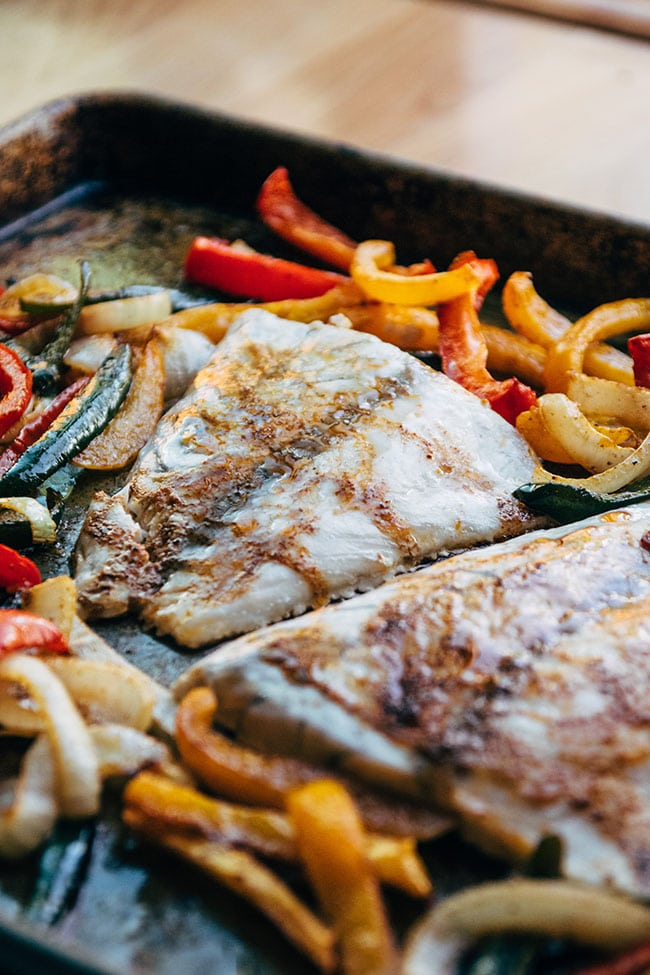 Baked barramundi fillets on a sheet pan with sliced bell peppers and onions.