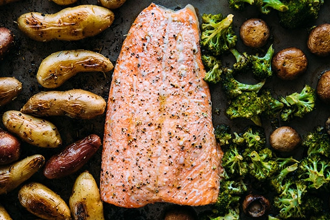 Baked salmon fillet on a sheet pan with roasted fingerling potatoes, broccoli, and mushrooms.