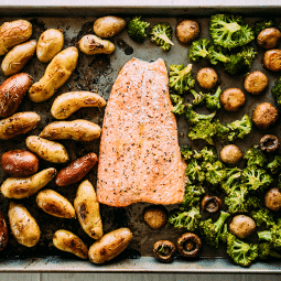 Overhead view of baked salmon, fingerling potatoes, and roasted broccoli on a sheet pan.