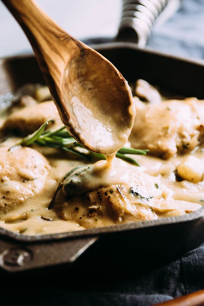 Wooden spoon drizzling sauce over chicken. Creamy garlic parmesan chicken and potato bake - a simple one pot chicken recipe with mushrooms, spinach, and a creamy garlic sauce.