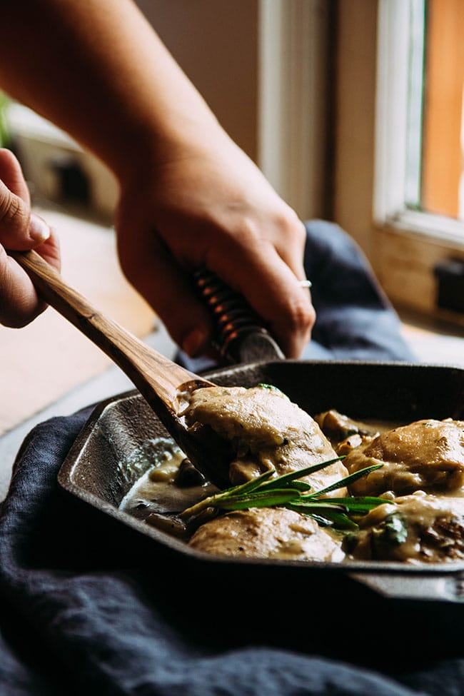 Hands using a wooden spoon to lift a piece of chicken out of a skillet.