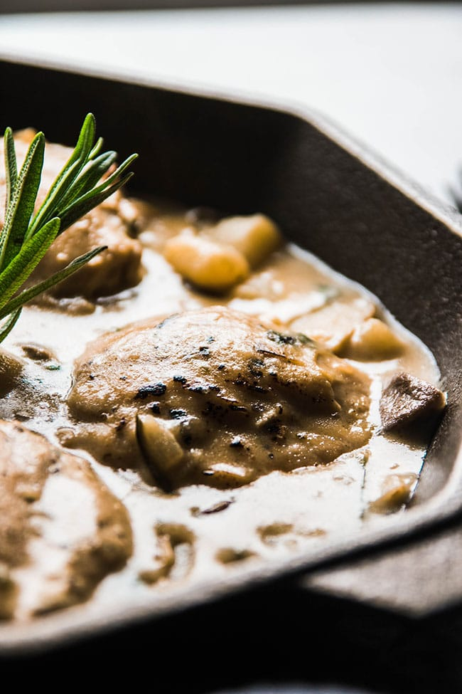 Close up of baked chicken and creamy sauce in a cast iron skillet.