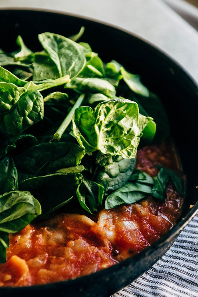 Fresh spinach being added to a cast iron skillet with tomato sauce.