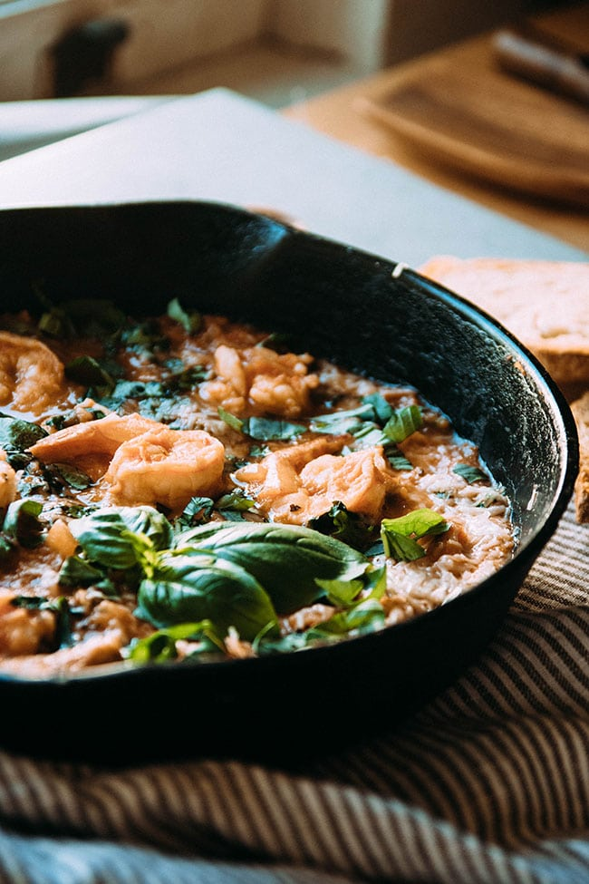 Shrimp and tomato sauce in a cast iron skillet, topped with a sprig of fresh basil.