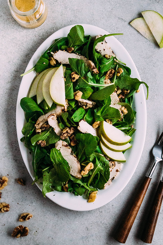 Overhead photo of arugula, pears, walnuts, and grilled chicken on a white ceramic platter with a light grey background.