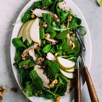 Overhead photo of a arugula salad on a white platter with grilled chicken, sliced pears, walnuts, and wooden handled silverware.