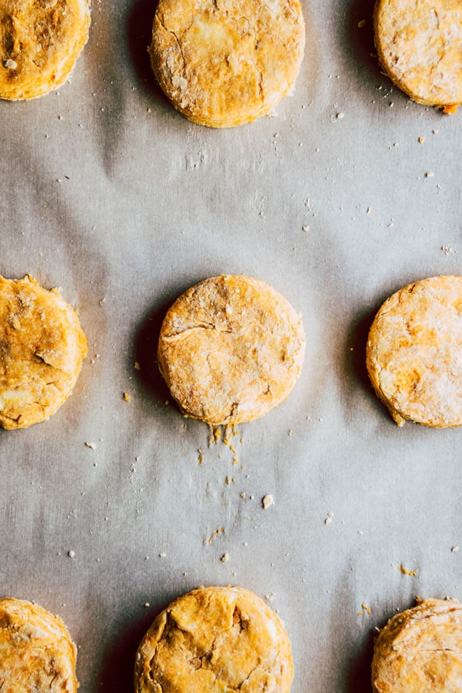 Overhead photo of raw biscuits on a parchment paper lined baking sheet.