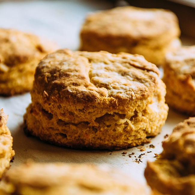 Side photograph of sweet potato biscuit on a baking sheet surrounded by other biscuits.