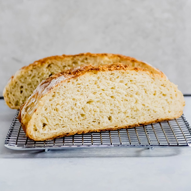 loaf of bread cut in half sitting on a wire cooling rack