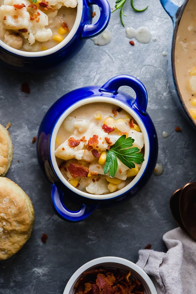 Two small blue bowls of fish chowder topped with bacon and parsley on a grey background.