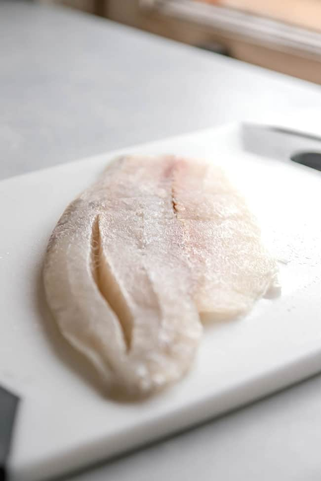 Uncooked barramundi fish fillet on a white cutting board.