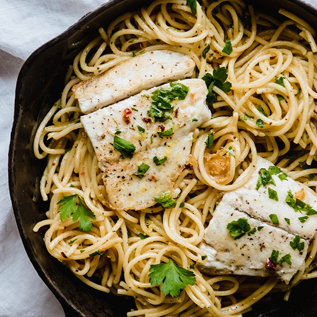 Overhead photo of spaghetti in a cast iron skillet topped with white fish and parsley