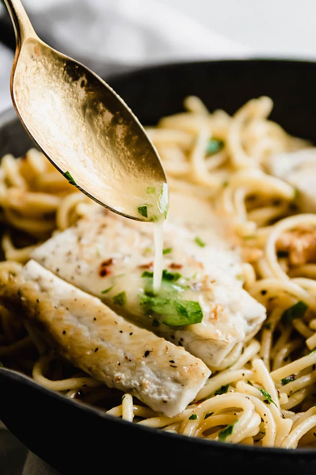 Gold spoon pouring melty butter over white fish atop spaghetti in a cast iron skillet