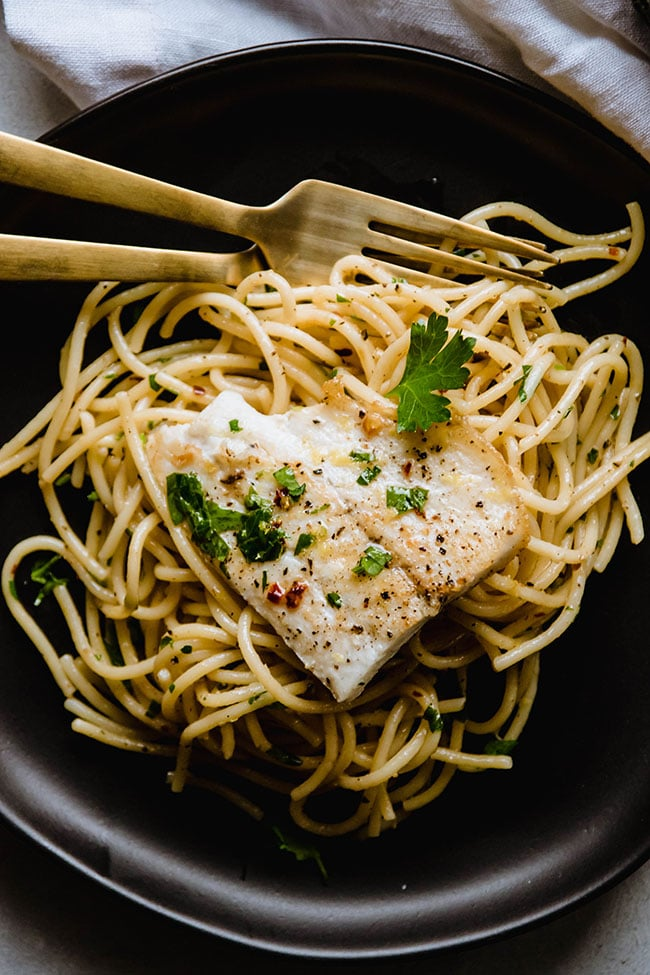 Overhead photo of plain spaghetti and seared white fish on a black plate with gold silverware
