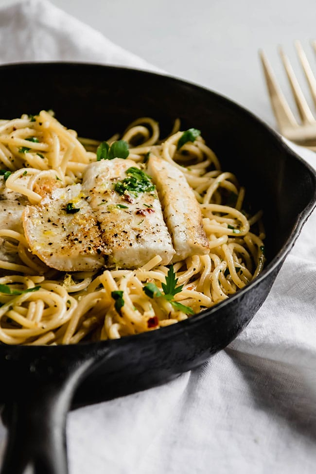 Cast iron skillet on a white background filled with pasta and seared white fish