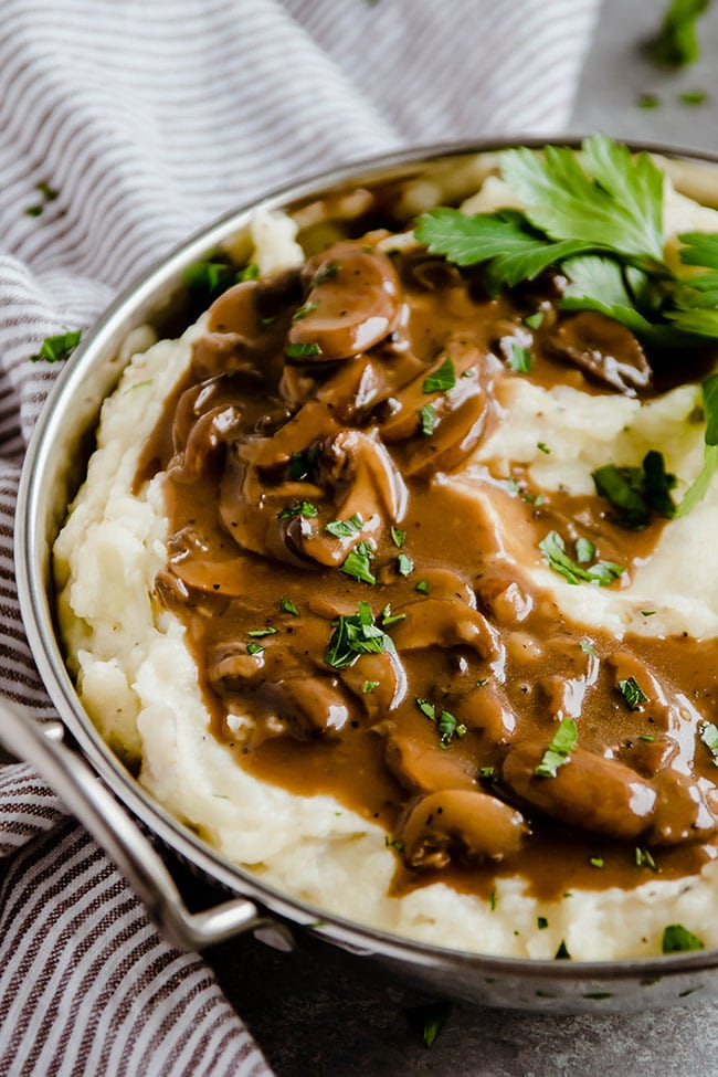 mashed potatoes in a metal pot topped with mushroom guinness gravy and fresh parsley